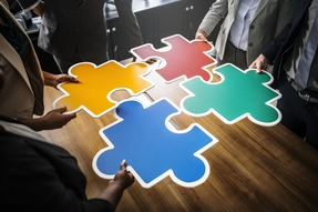Jigsaw puzzle pieces in different colours, table and people.